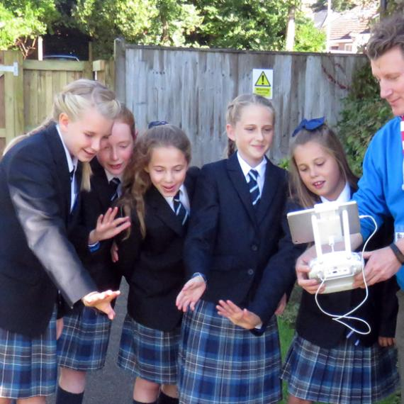 Year 7 girls try out the iPad controls of the drone with pilot Tim Squires